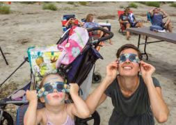 Curry Ernst and daughter Penny observe the solar eclipse from Sullivan's Island beach