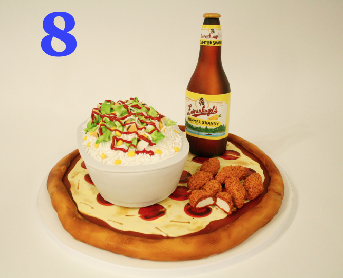Cakes that look like other foods are some of the most fun to make! We think it's the playfulness of one food item (cake) disguised as another. It's especially fun when we make something sweet look like something savory. This junk food cake has all the classics (pizza, wings, beer, and a Chipotle burrito bowl. And yes, this decorator did go out and get Chipotle after finishing the cake!