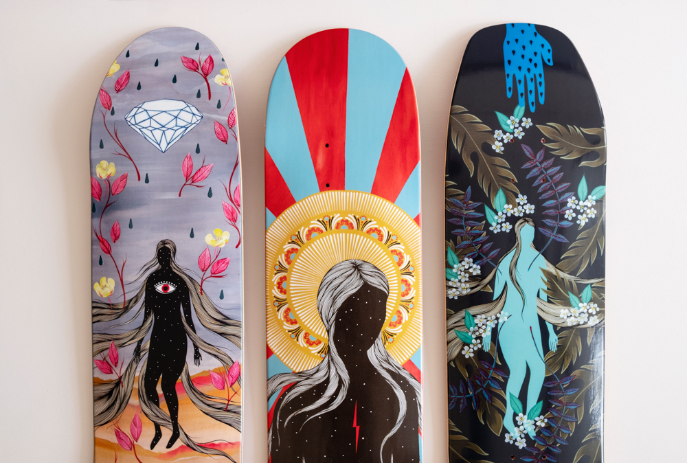 Flat lay of three skateboard decks depicting art by Hannah Dansie. Local artist available for commercial projects.