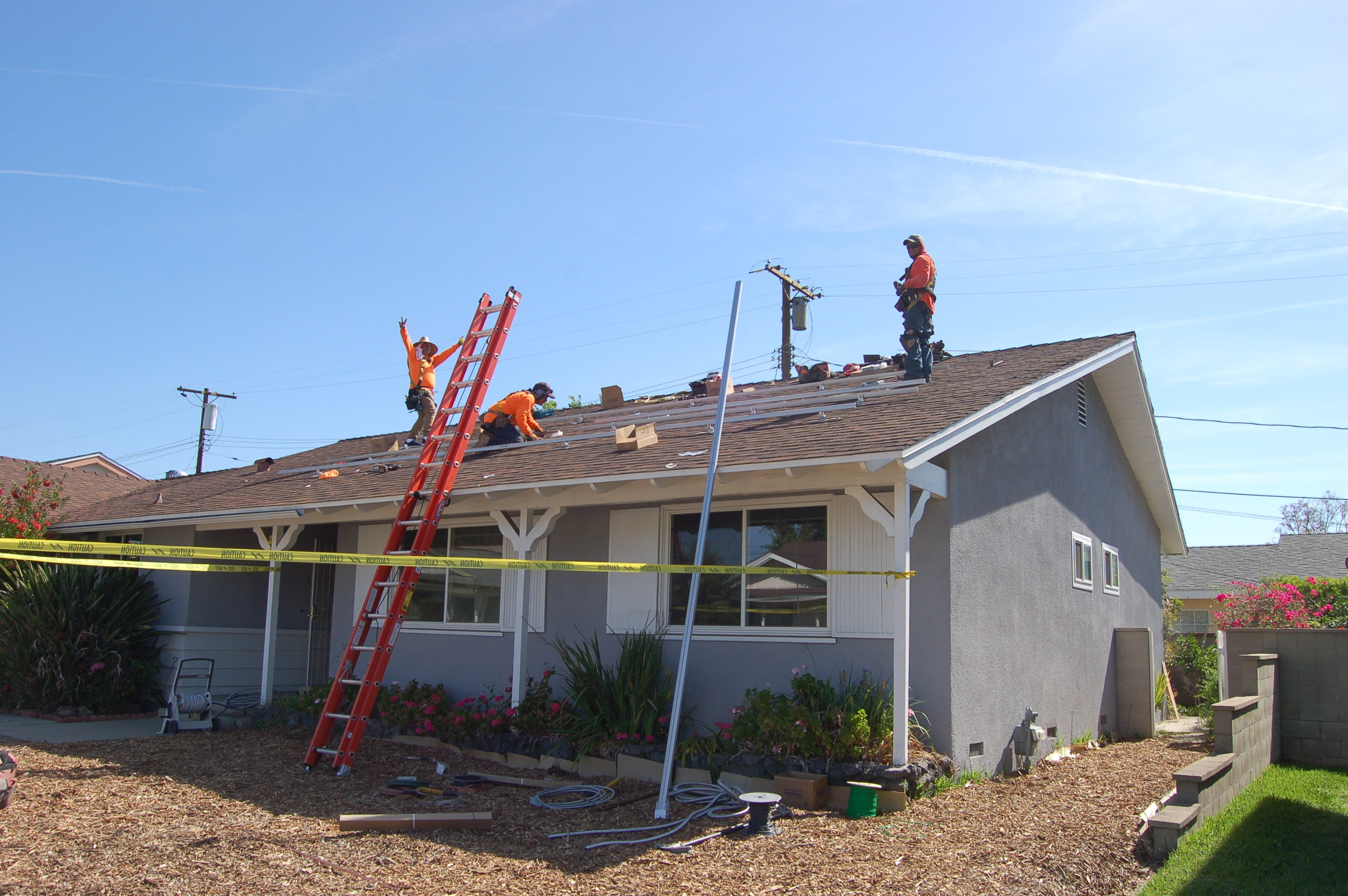 A local solar company putting supports for PV panels on our roof. No that's not a tiny man on the ladder.