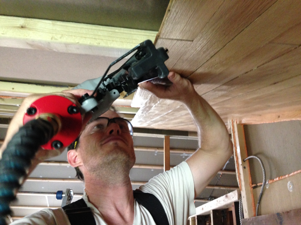 Chris blind nails the paneling into a furring strip using a 16-guage pneumatic brad nailer.