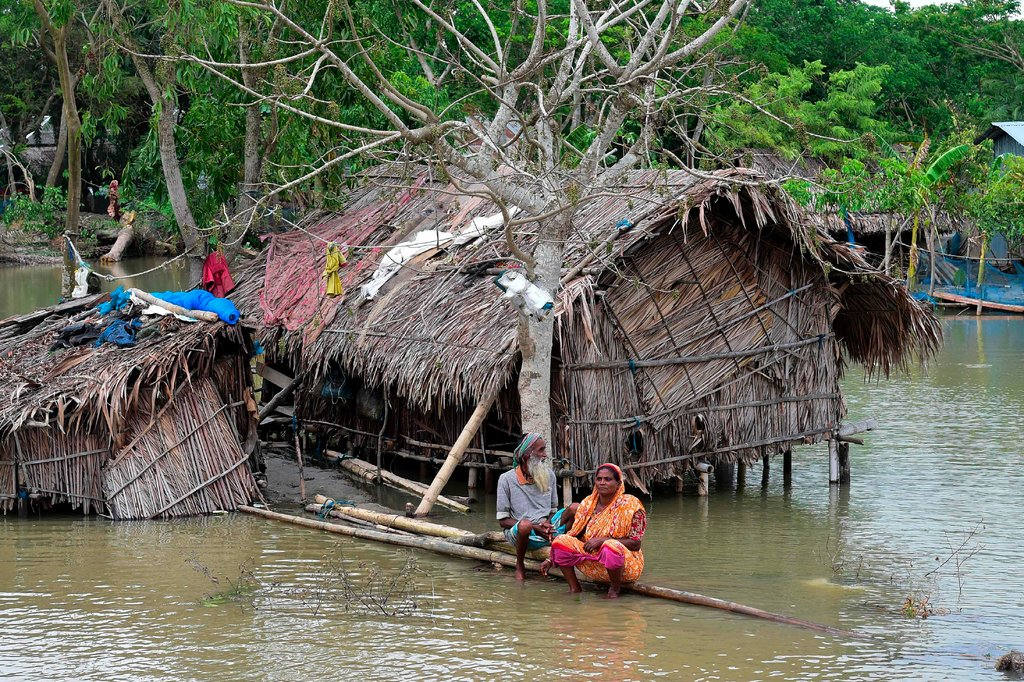 A couple sat marooned by high water on Saturday in Khulna, Bangladesh [Munir Uz Zaman/Agence France-Presse — Getty Images]