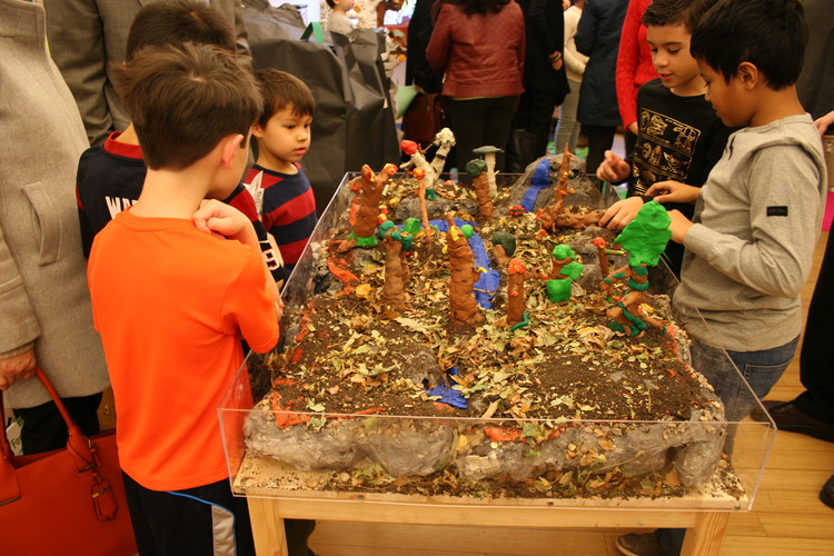 8/9s students share their work with a young visitor during last year's december culmination