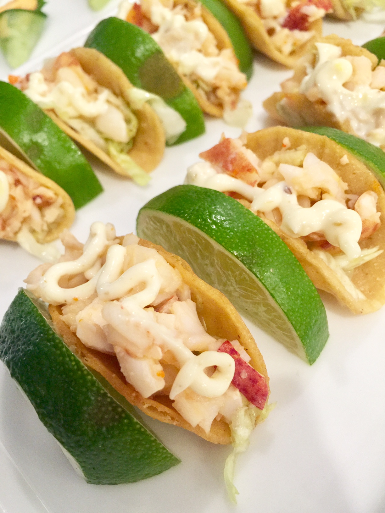 Mini Lobster Salad Tacos topped with a Lime Creme Fraiche
