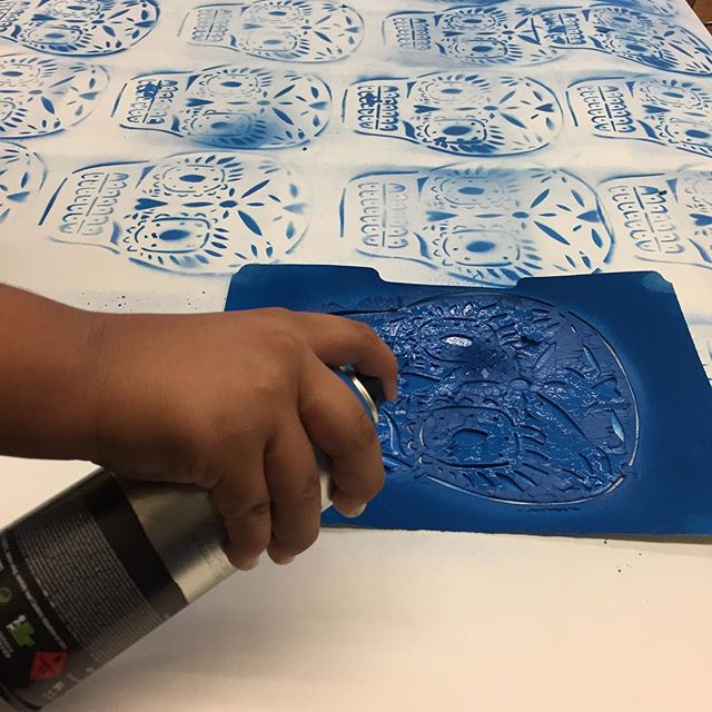 4th graders at Telpochcalli Elementary spray painting stencils to make Day of the Dead designs.
