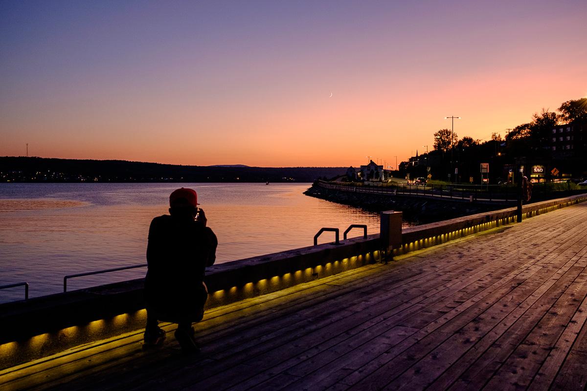 Louis qui prend en photo le coucher de soleil avec un minuscule croissant de lune.