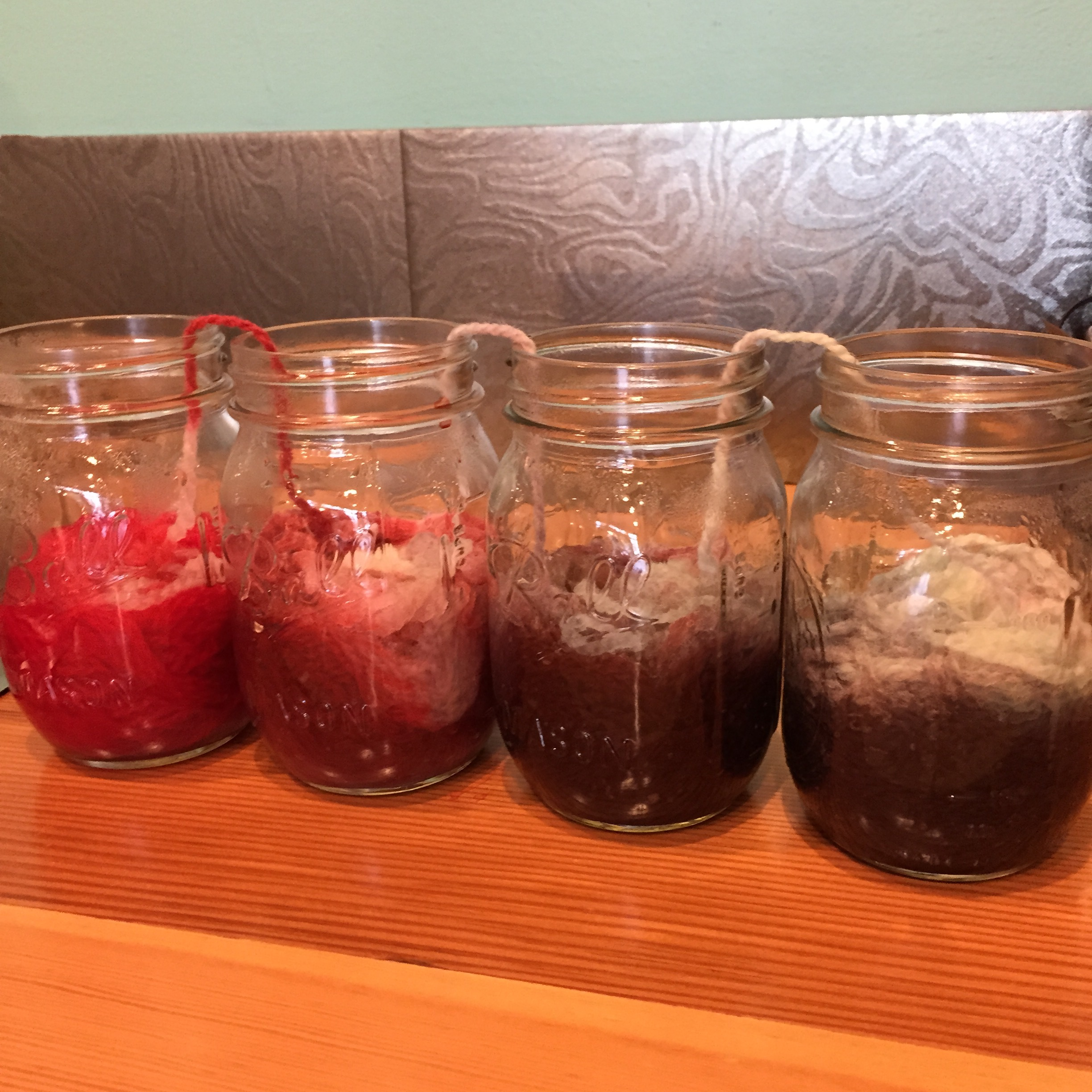 I shoved the balls of yarn into the jars and quickly realized that I hadn't added enough water. (See the white yarn?) I tried to add more water, but the dye had already migrated into the yarn and out of the water.  Oh well, I was pretty sure it would still look cool.