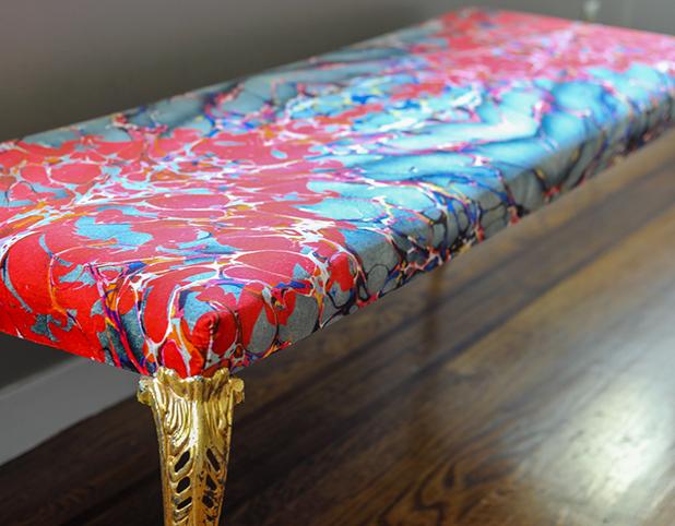 """Revitaliste custom upholstered this Gilded Leg Bench in Timorous Beasties """"Ex Libris"""" velvet in Brick."""