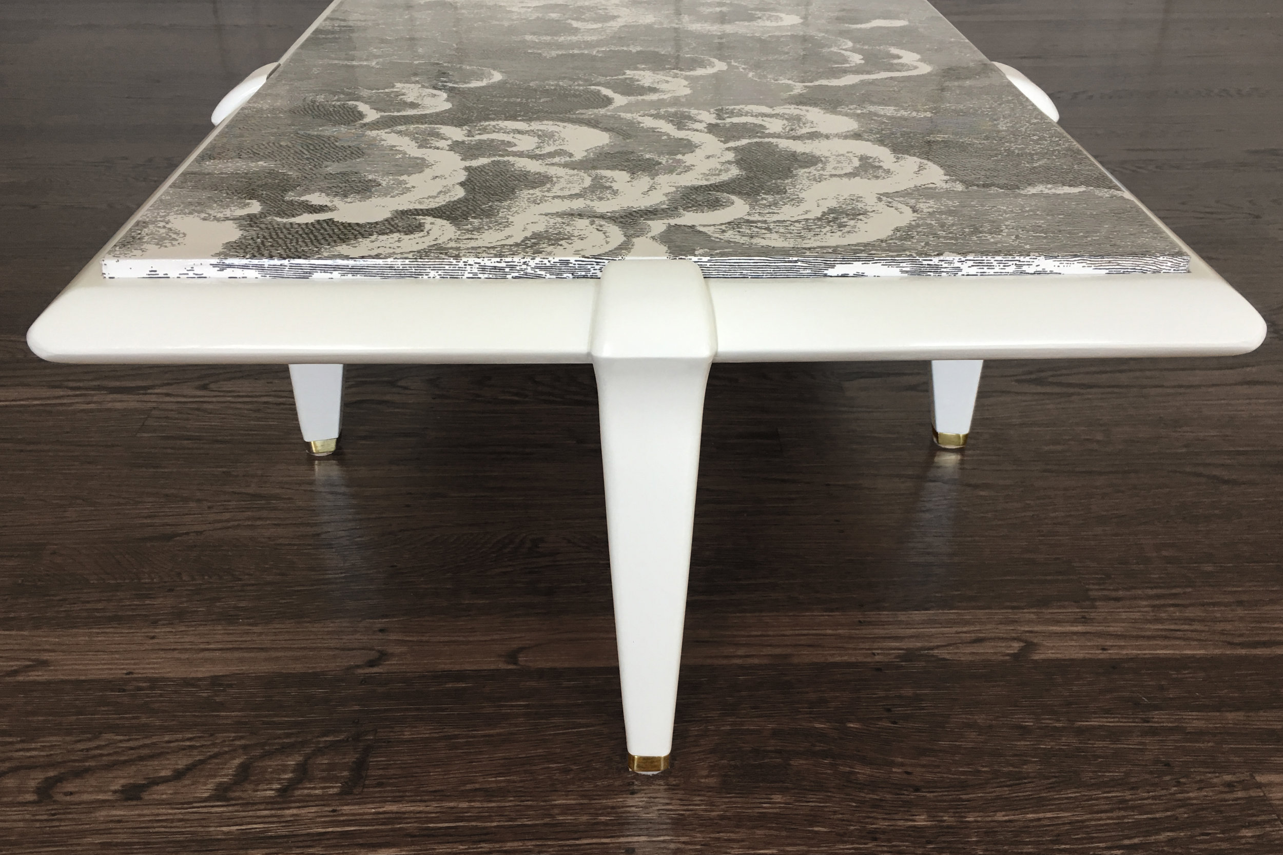 """Revitaliste refinished this Mid-Century Modern Coffee Table with a high gloss white lacquer and wrapped the table top in Fornasetti wallpaper """"Nuvolette"""" then sealed with a high gloss clear coat."""