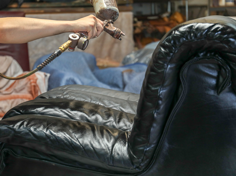 A stain being applied to the leather De Sede sofa during reconditioning process