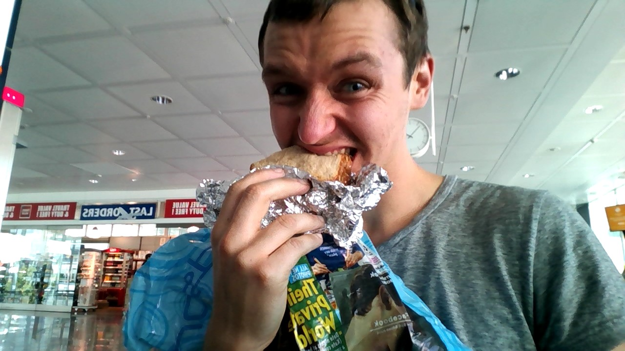 Biting down on my last US sandwich (~24 hours old) while chilling in Munich. Delicious. Also pictured: my carry-on bag. I've taken to clutching it to my breast, since I don't trust the handles.