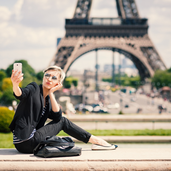 Happy young woman taking a selfie with mobile phone in Paris, Fr