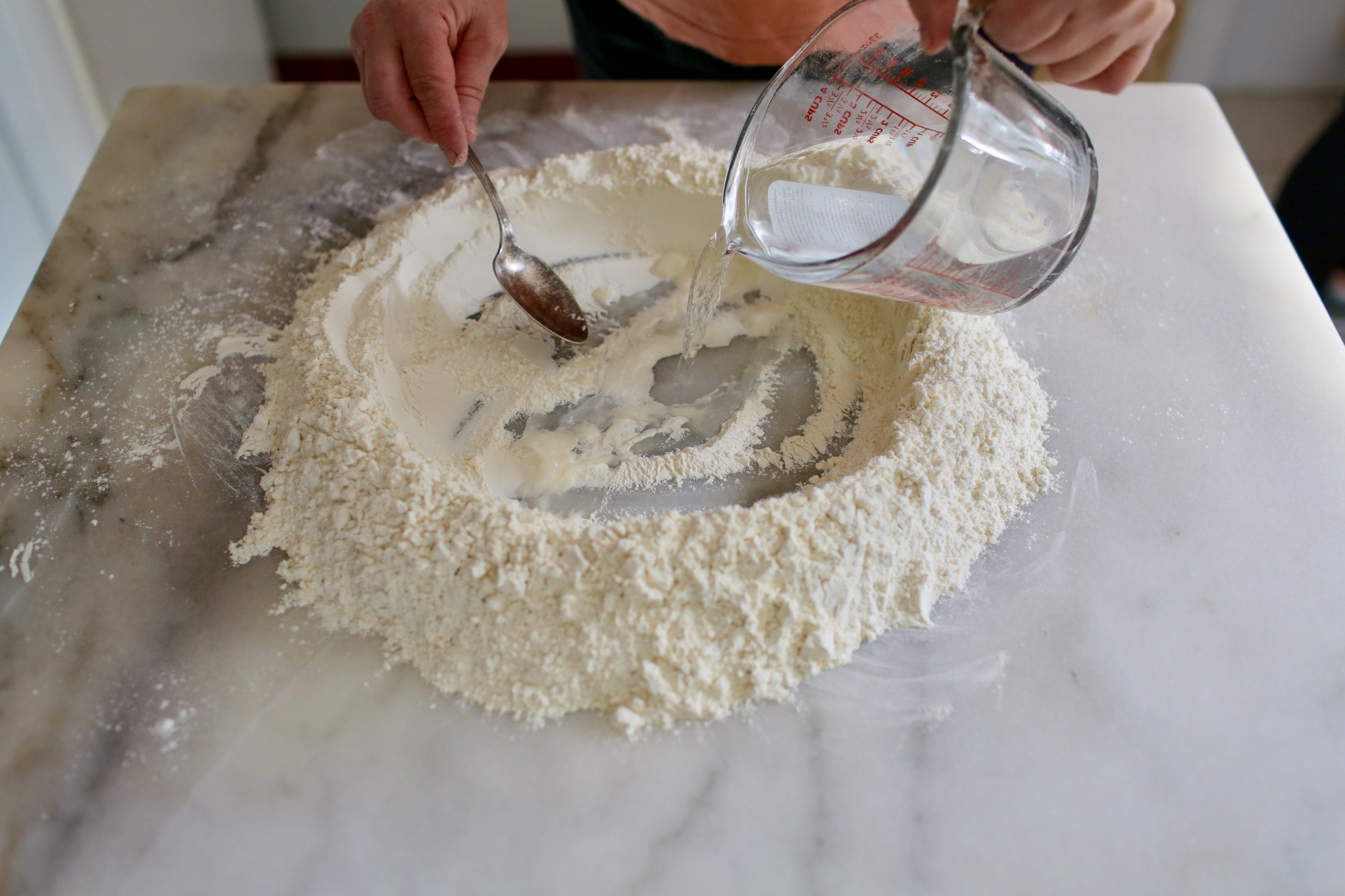 1. For dough, make a well in the flour and add water and salt.