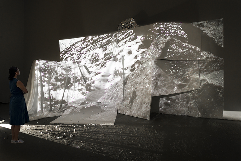 """Allison Hunter, installation view, """"Encounters,"""" 2018, 2-channel video installation with paper, foil, cloth, saw horse, wood panel, VSC Open Studios, Johnson, VT."""