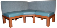 Madiera Designer Banquette  Displayed In: Blue Vinyl, Chenille Back   Dimensions:   L:60″ x 60″  D: 26″  H: 36″   Available in custom sizes & fabrics.   This banquette boasts classic lines and a plush sectioned cushioning that creates a solid but sleek.  A wedge-shaped corner provides an additional seat for your dining patron.  This piece is also available with closed ends or Parson's legs..