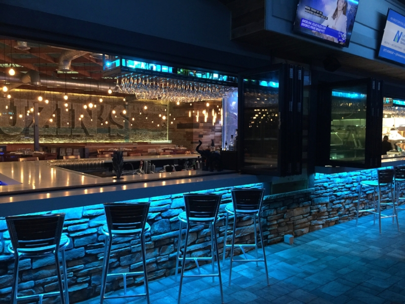 At Cuzin's, Restaurant Designer Raymond Added bifold windows to open the interior bar to the outside patio