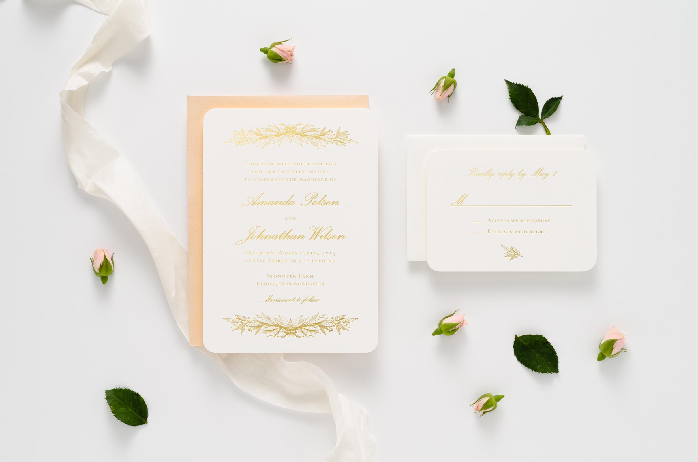 Elegant gold foil wedding invitation suite with decorative botanical accents