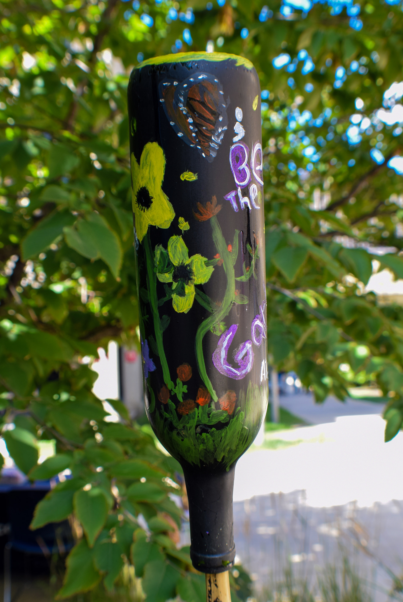 Umair's bottle with plants and monarch butterflies in a dark sky background.