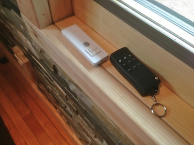 White remote is for overhead halogen lights. Black remote is for turning on white LED lights on trees outside.