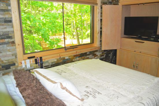The bed overlooks the forest.