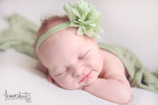newborn baby girl sleeping on her hands wearing a green headband