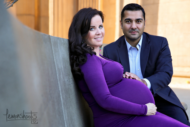 expecting couple touching pregnant belly at palace of fine arts