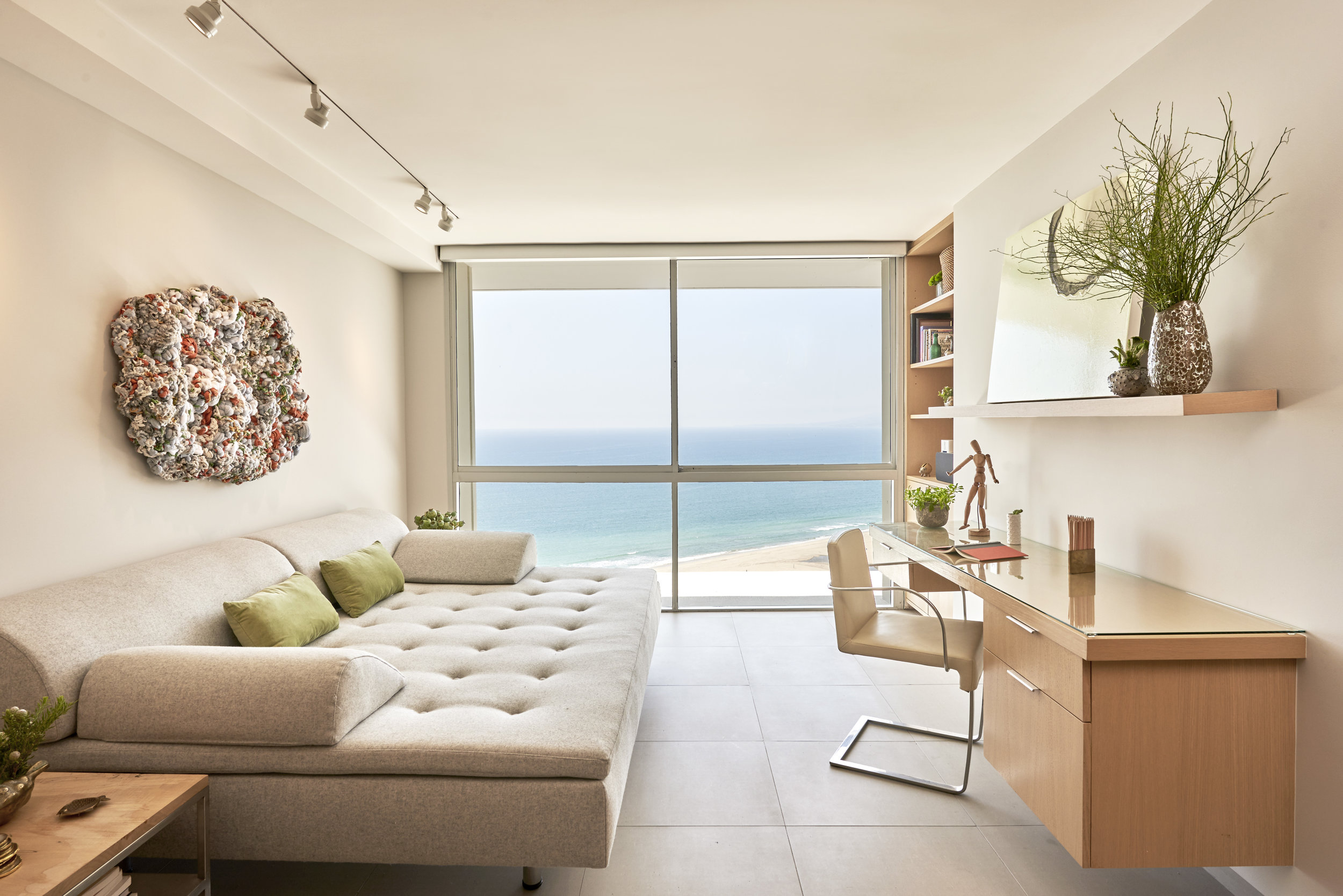 Sarah Barnard uses the ocean as a focal point of this Ocean Avenue penthouse living room by utilizing a beautiful neutral color scheme that prevents the eye from becoming too distracted or strained.