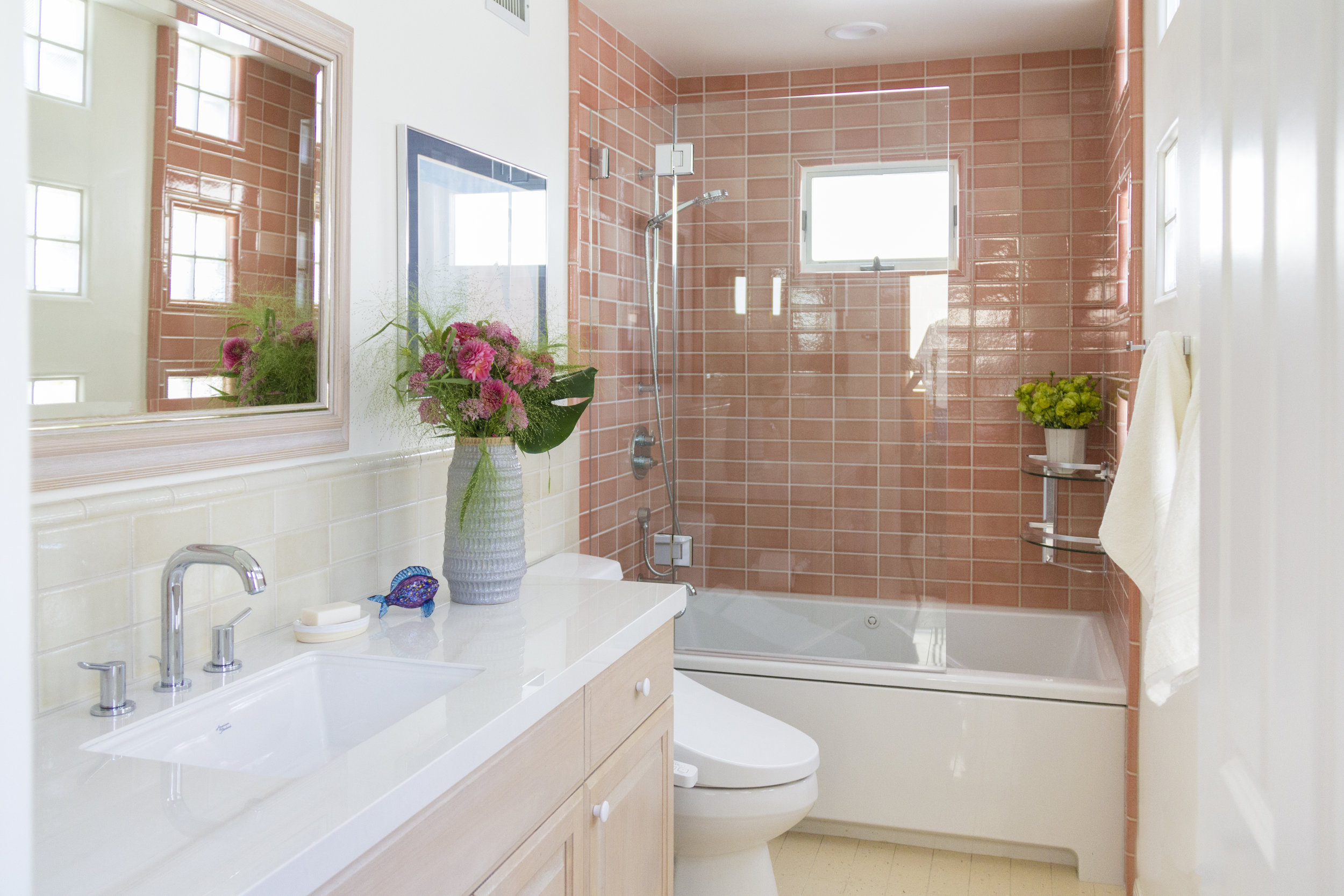 Coral colored tiles and beautiful glossy stone slabs make this coastal bathroom warm and bright.