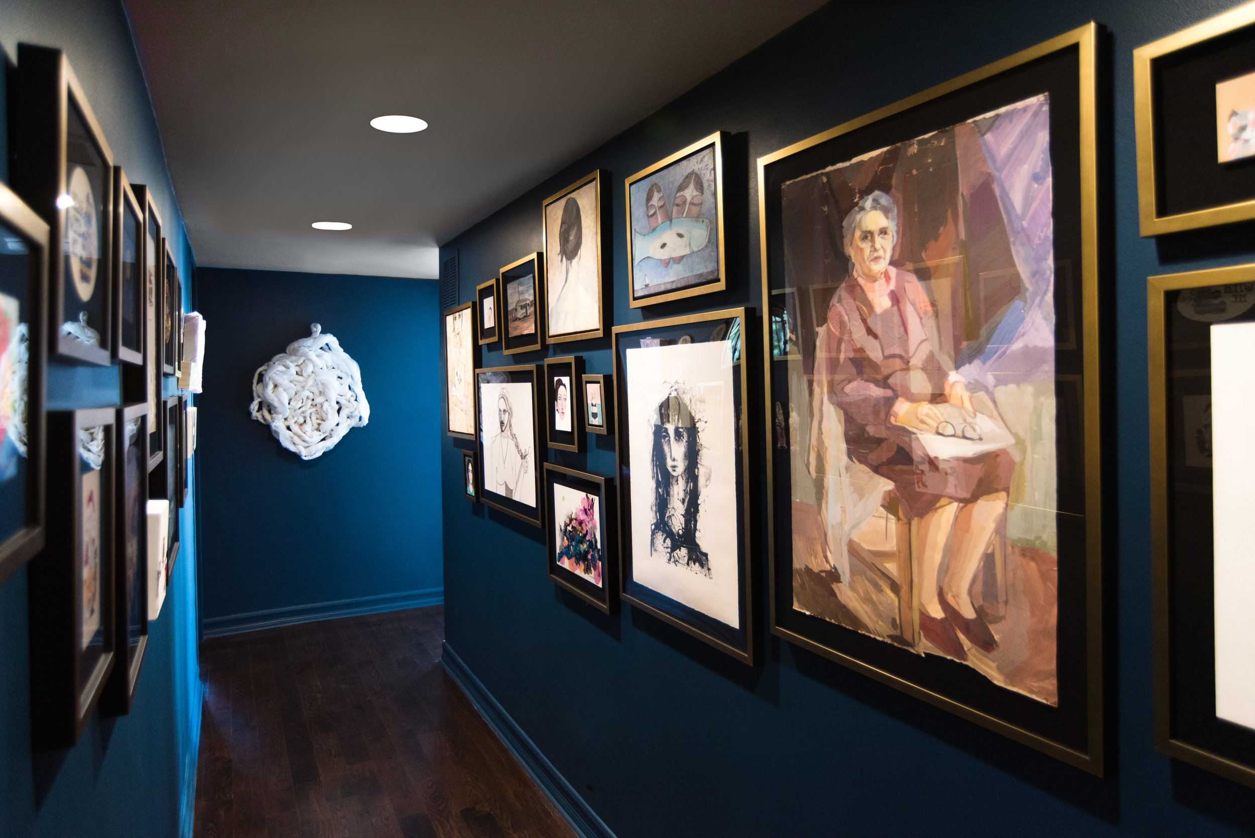 Brushed gold and black frames pop against the bold wall color and unify the homeowner's art collection.