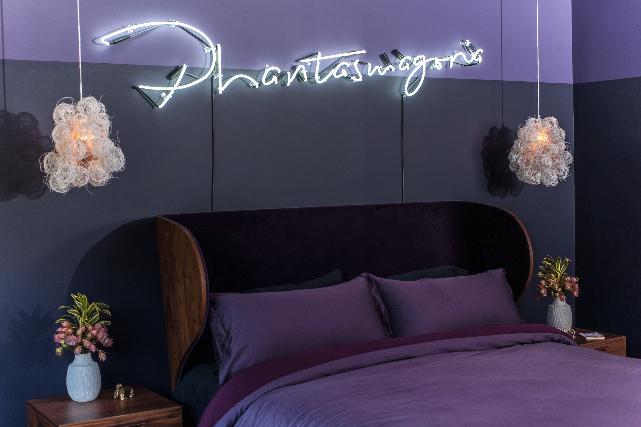 California king bed made from award-winning, American black walnut by Autoban, lined with purple velvet, blending natural textures with dark, feminine styling. Above it, a custom neon piece reading 'Phantasmagoria' adds an ethereal glow.