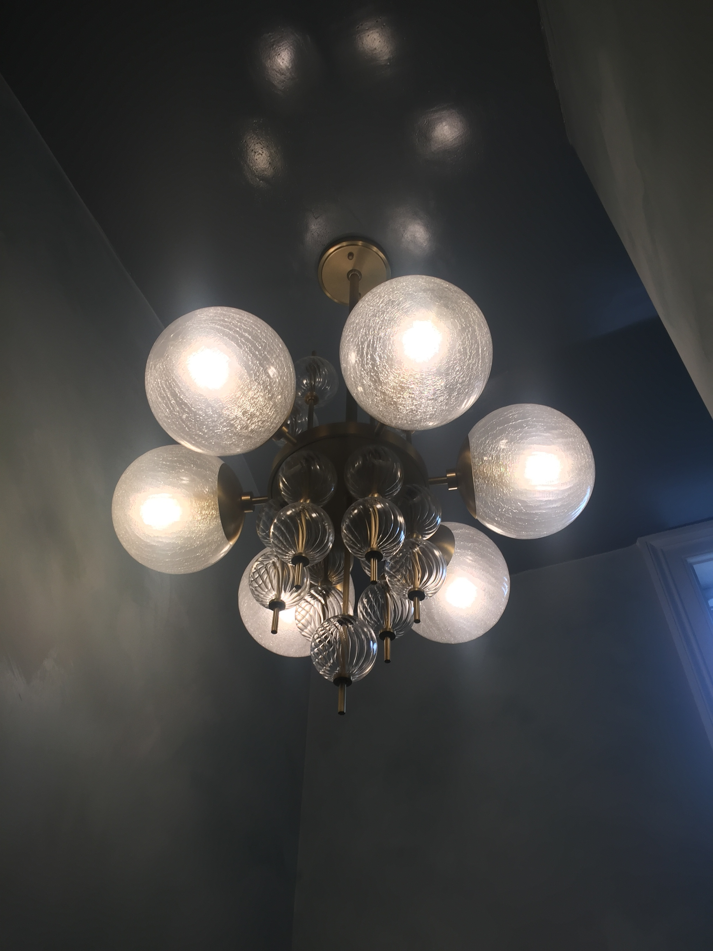A brilliant brass and glass orb chandelier designed by Corey Damen Jenkins for Hudson Valley Lighting pops against the deep wall color.