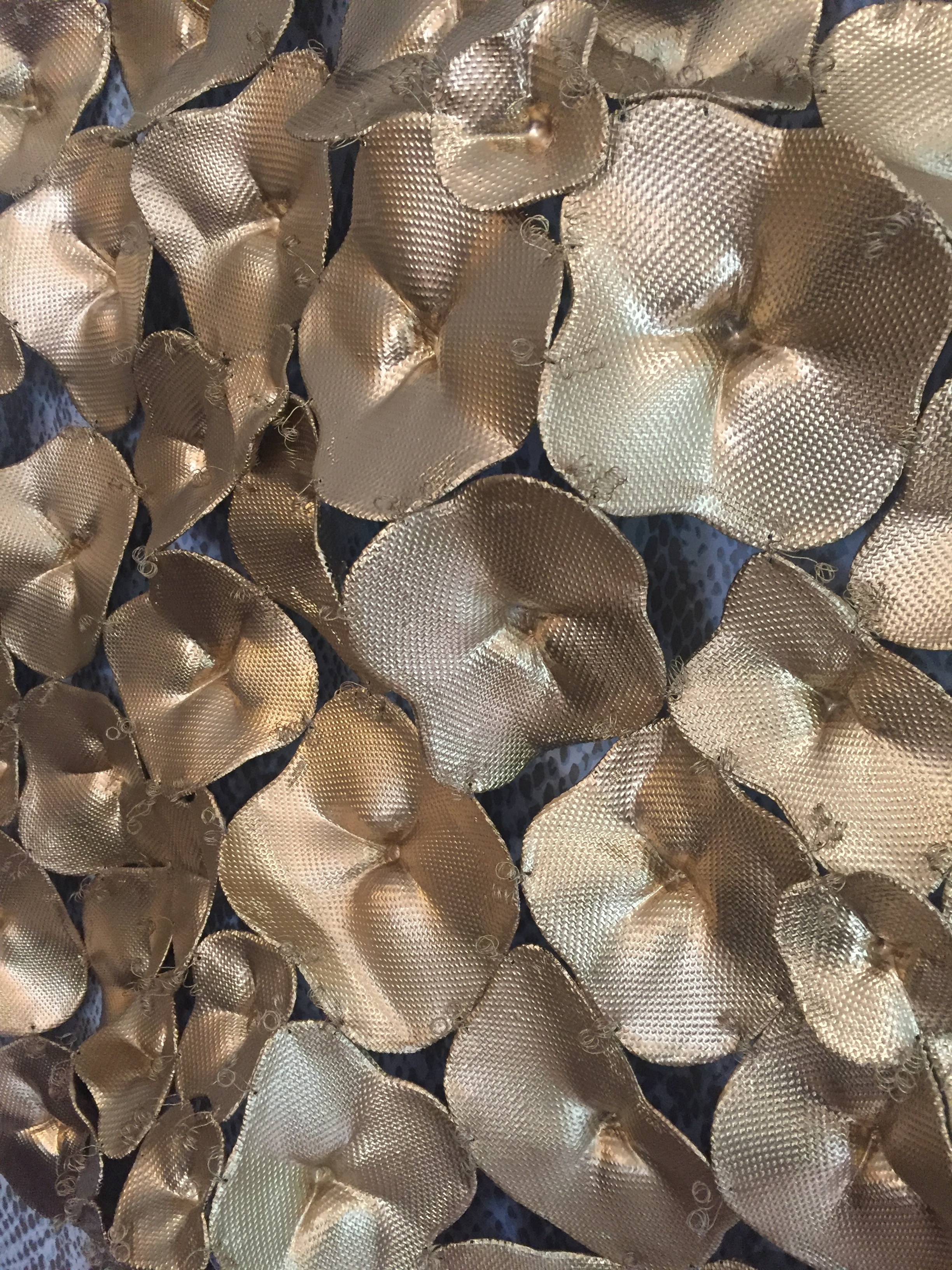 This metallic wall sculpture consists of individual handmade pieces reminiscent of flowers.