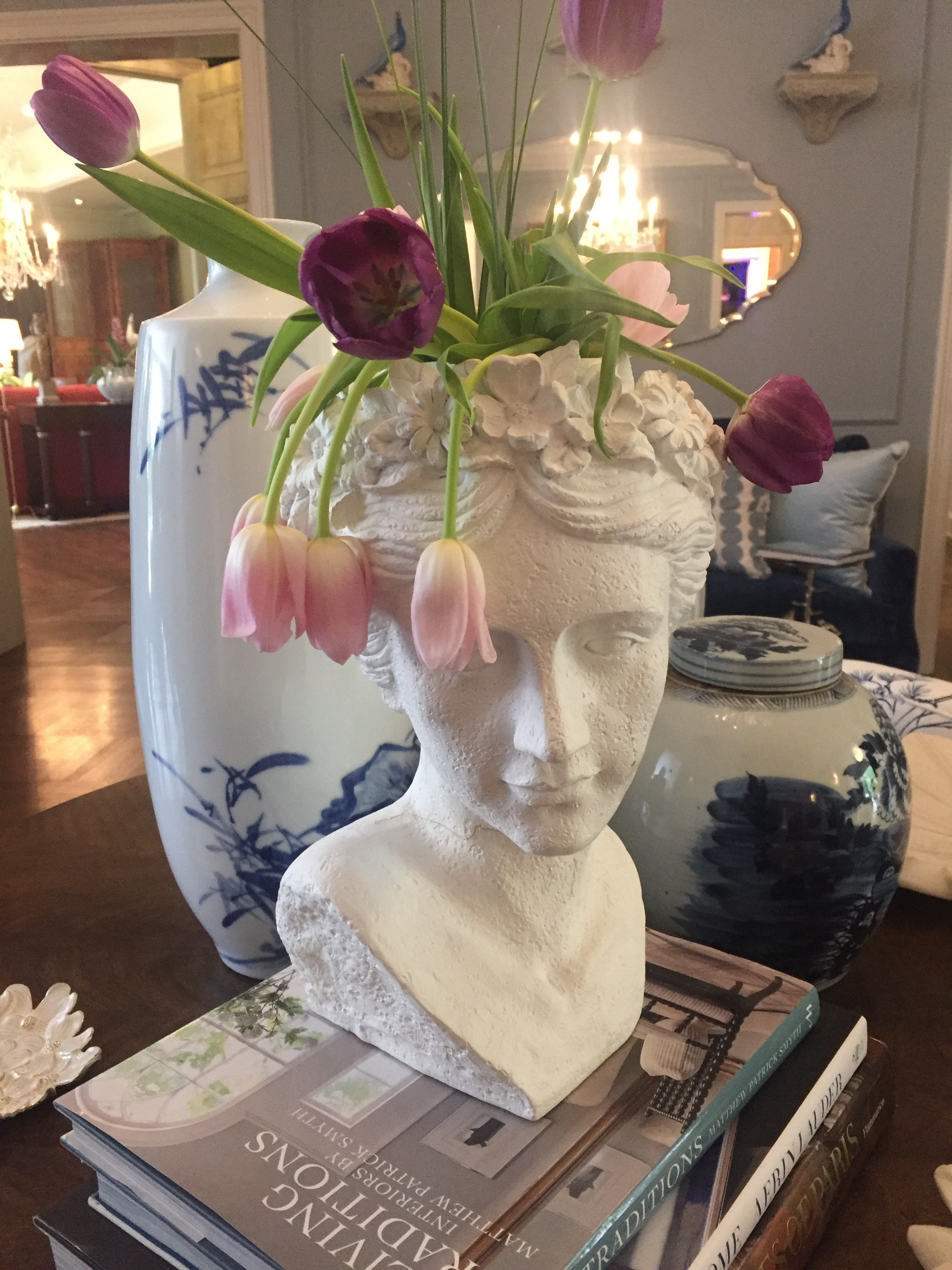 A plaster cast bust doubles as a planter displaying fresh cut tulips.