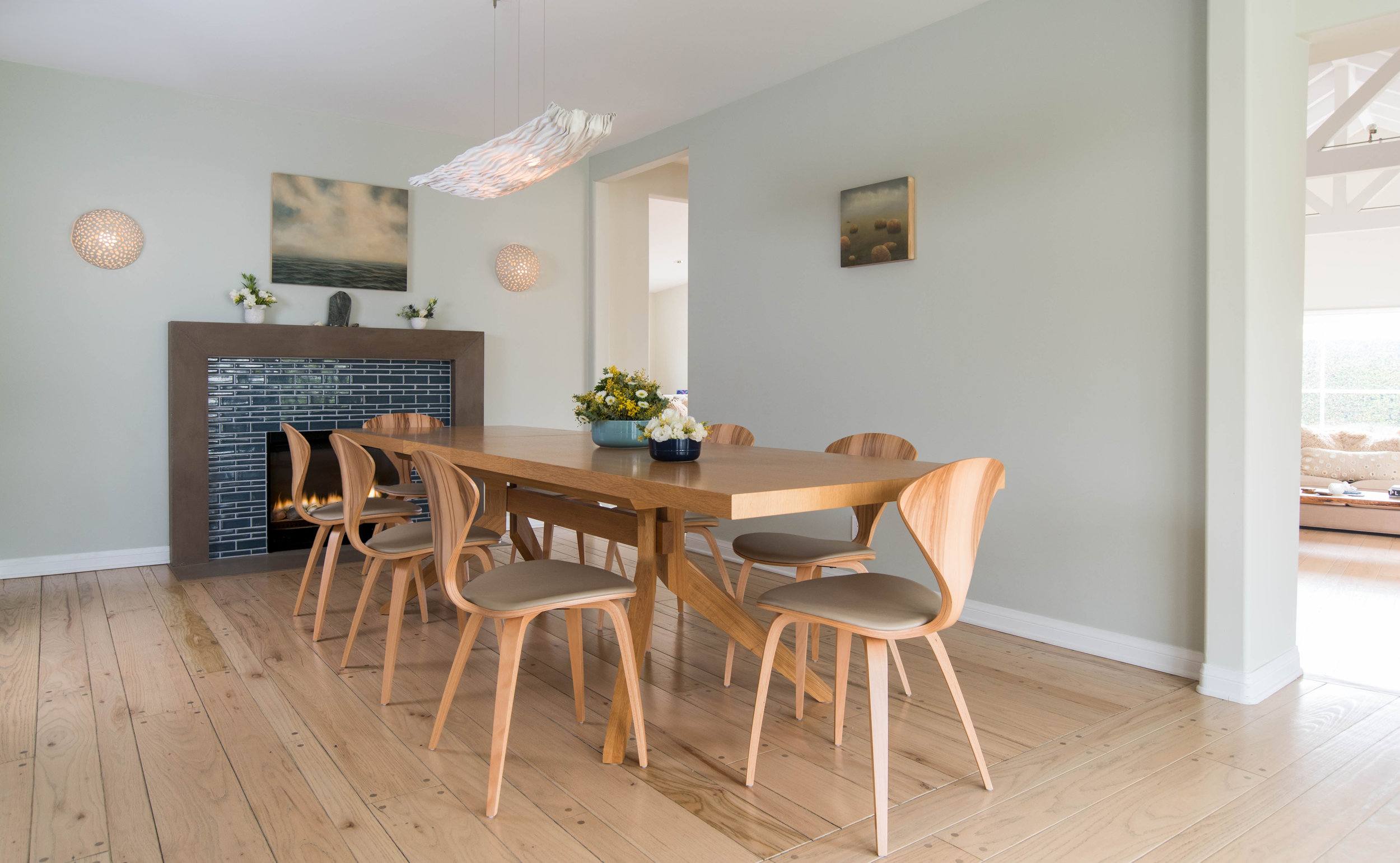 Natural dining chairs by the Cherner Chair Company have a slim silhouette.