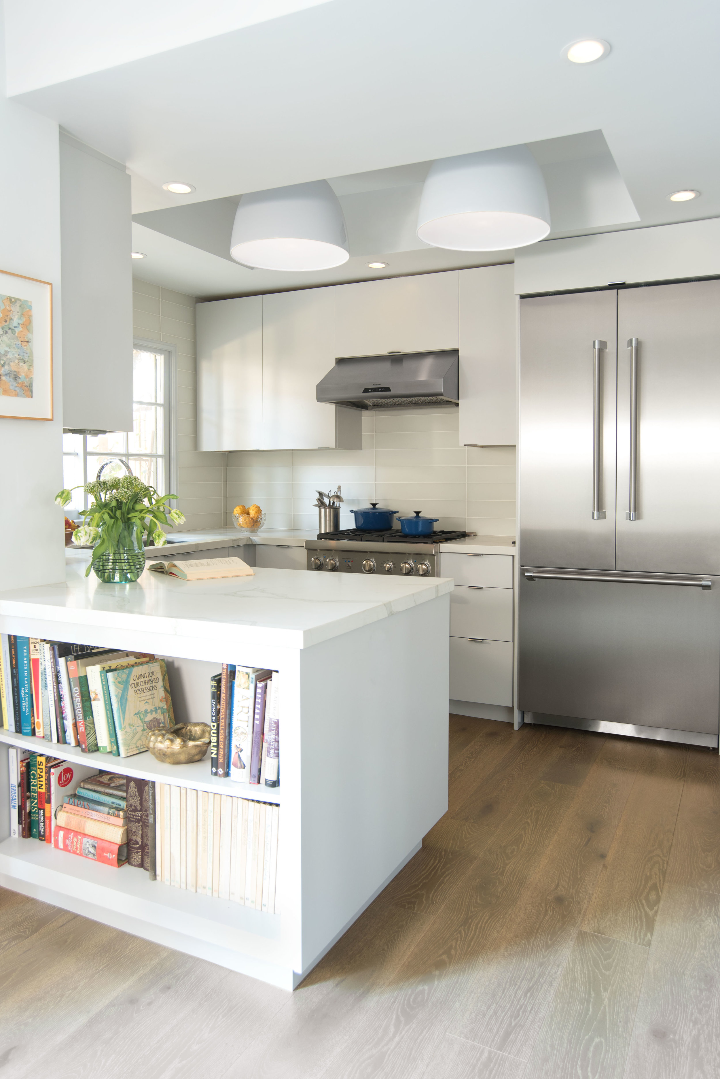 A tidy, minimalist kitchen in with open shelving to keep cookbooks close at hand.