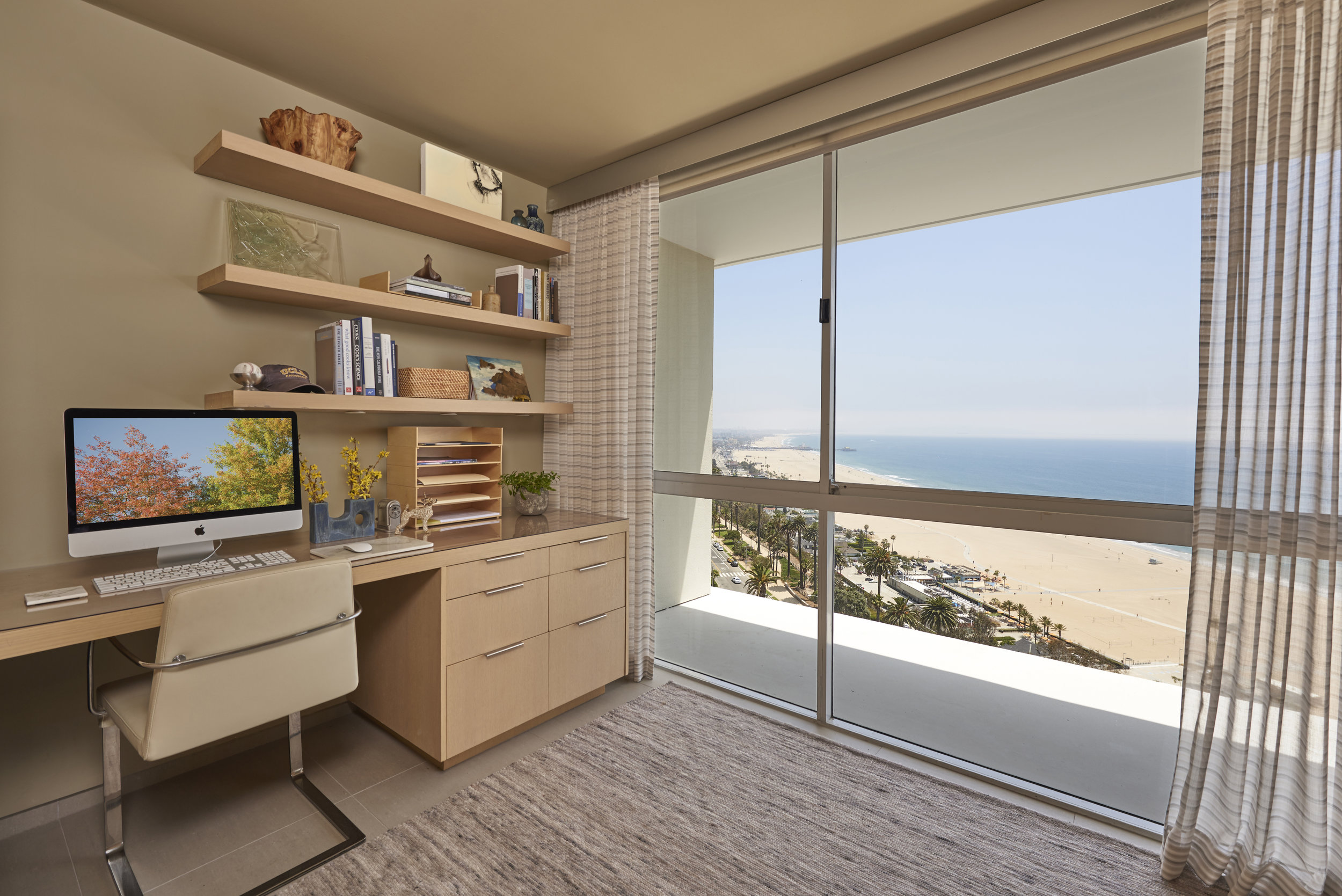 Floating shelves provide vertical storage in this compact home office featuring an impressive view of the Santa Monica shoreline.
