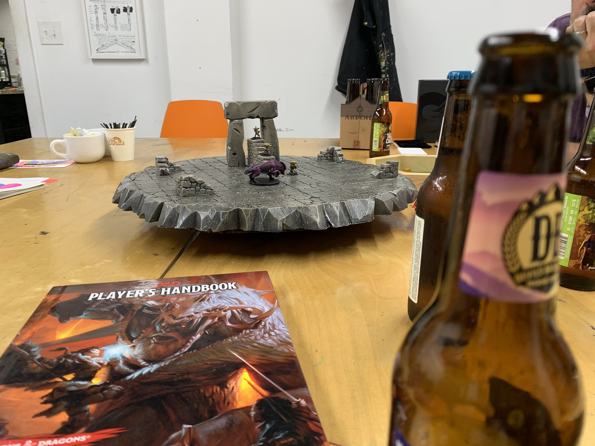 A picture of D&D miniatures and environment created by our friend Scott. There's a Player's Handbook and a beer bottle in the foreground.