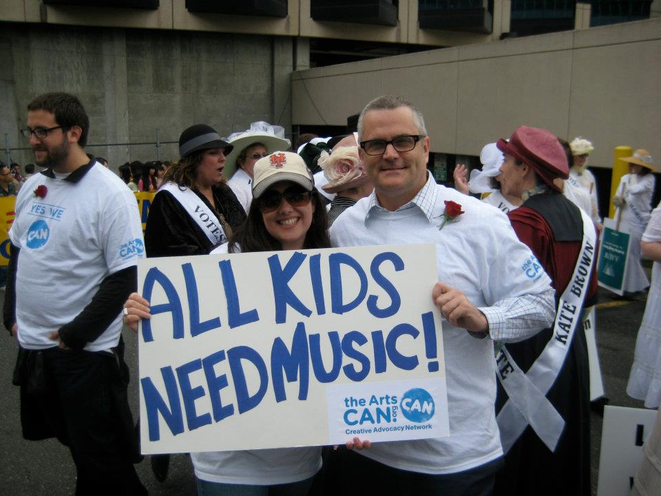 Kristin and Former Portland Mayor Sam Adams advocate for arts funding while marching in the 2012 Grand Floral Parade.