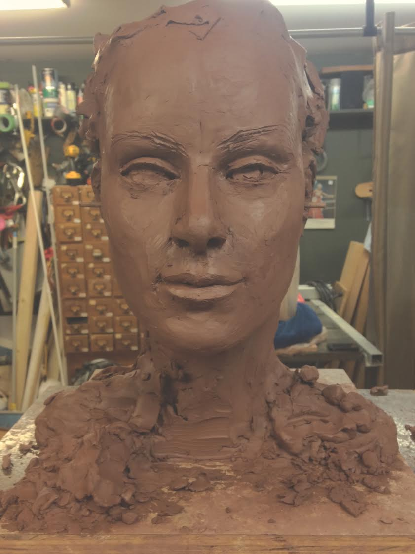 "This is what once was a hunk of clay, turned semi face shaped, turned almost complete bust that we are working on. ""We"" being a loose term, he does 99% of the work."