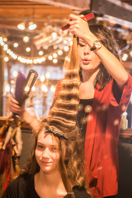 Hairstylist,Jacqueline Gibert prepping her model's hair for a runway styling, photograph by Robert Berlin