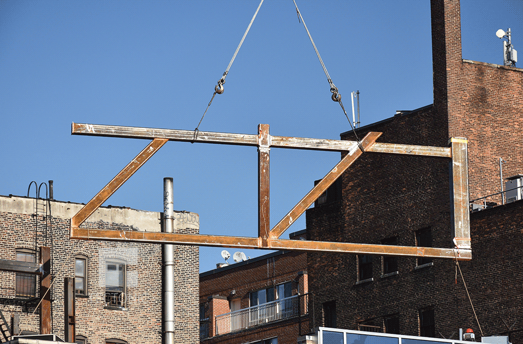 Steel frame section being lifted into place