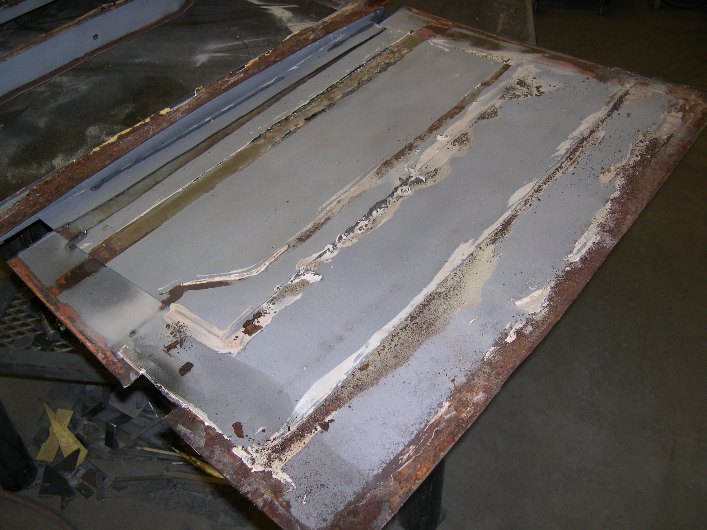 """BEFORE: Here's how the old """"restoration"""" of the door skins looked. Lap welded patch panels covered in seam sealer on the inside and lots of Bondo on the outside."""
