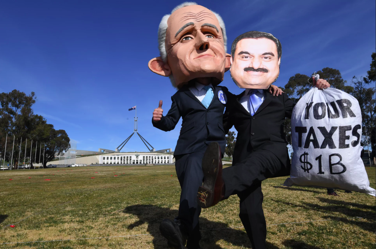 Men wearing masks of Australian prime minister Malcolm Turnbull and Adani chairman Gautam Adani protest outside Parliament House in Canberra. Photograph: Lukas Coch/AAP