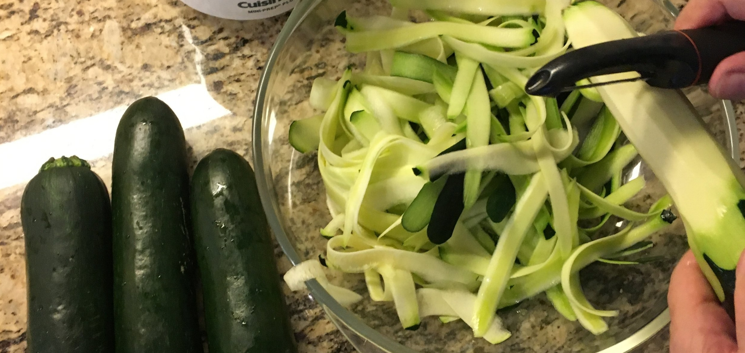 Using a standard peeler to make zoodles. You can also use a sharp knife to cut zucchini into super thin strips.