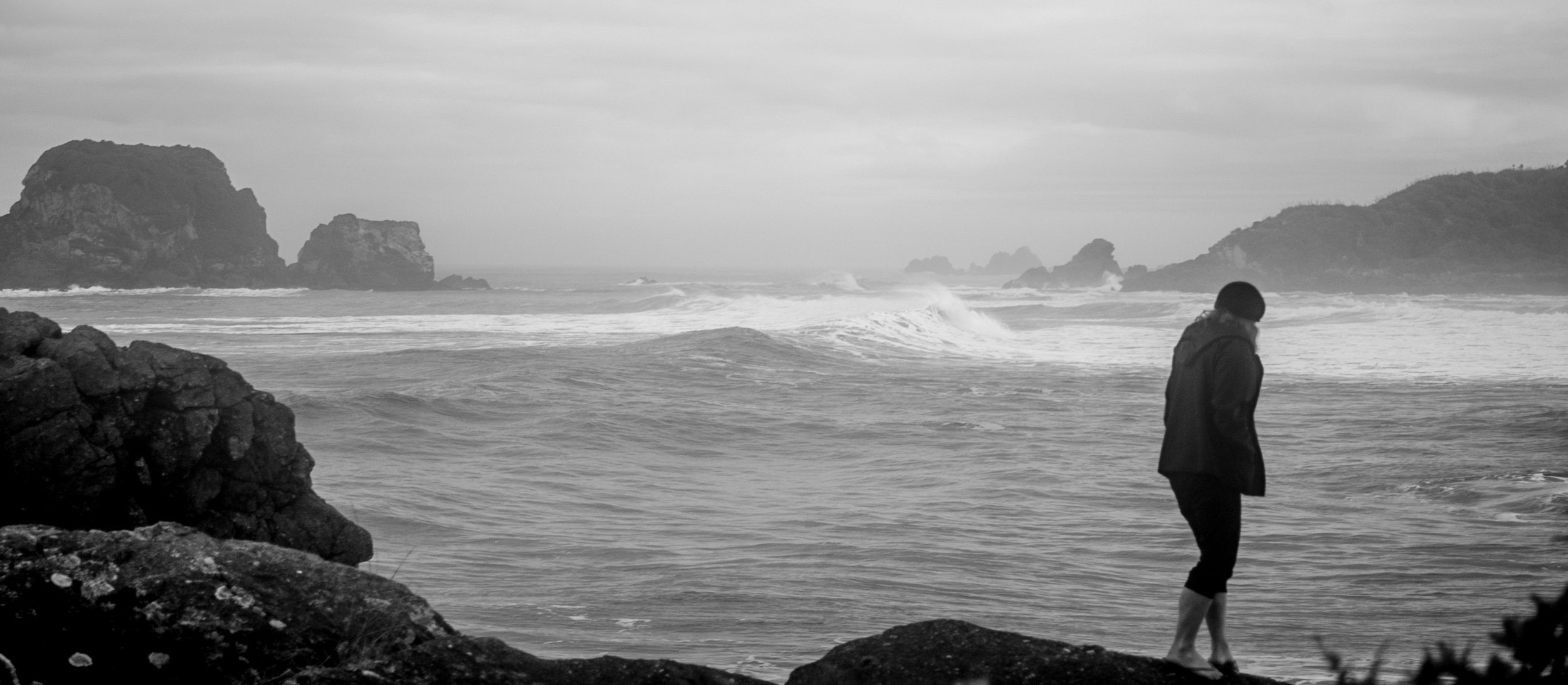 Surf, swell and spray at Tauranga Bay, Cape Foulwind in the distance.