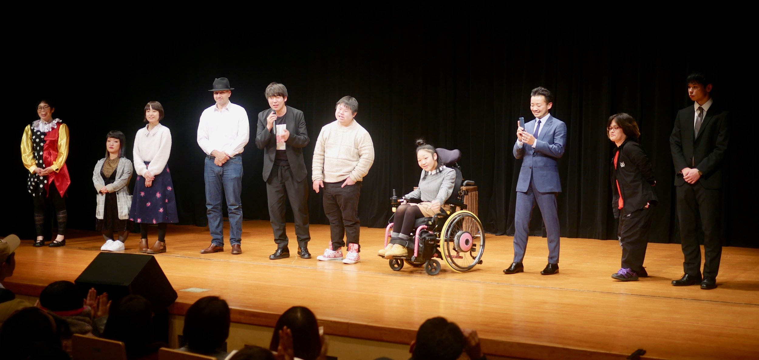 Performers take a curtain call with Muramoto Daisuke (in black with mic).