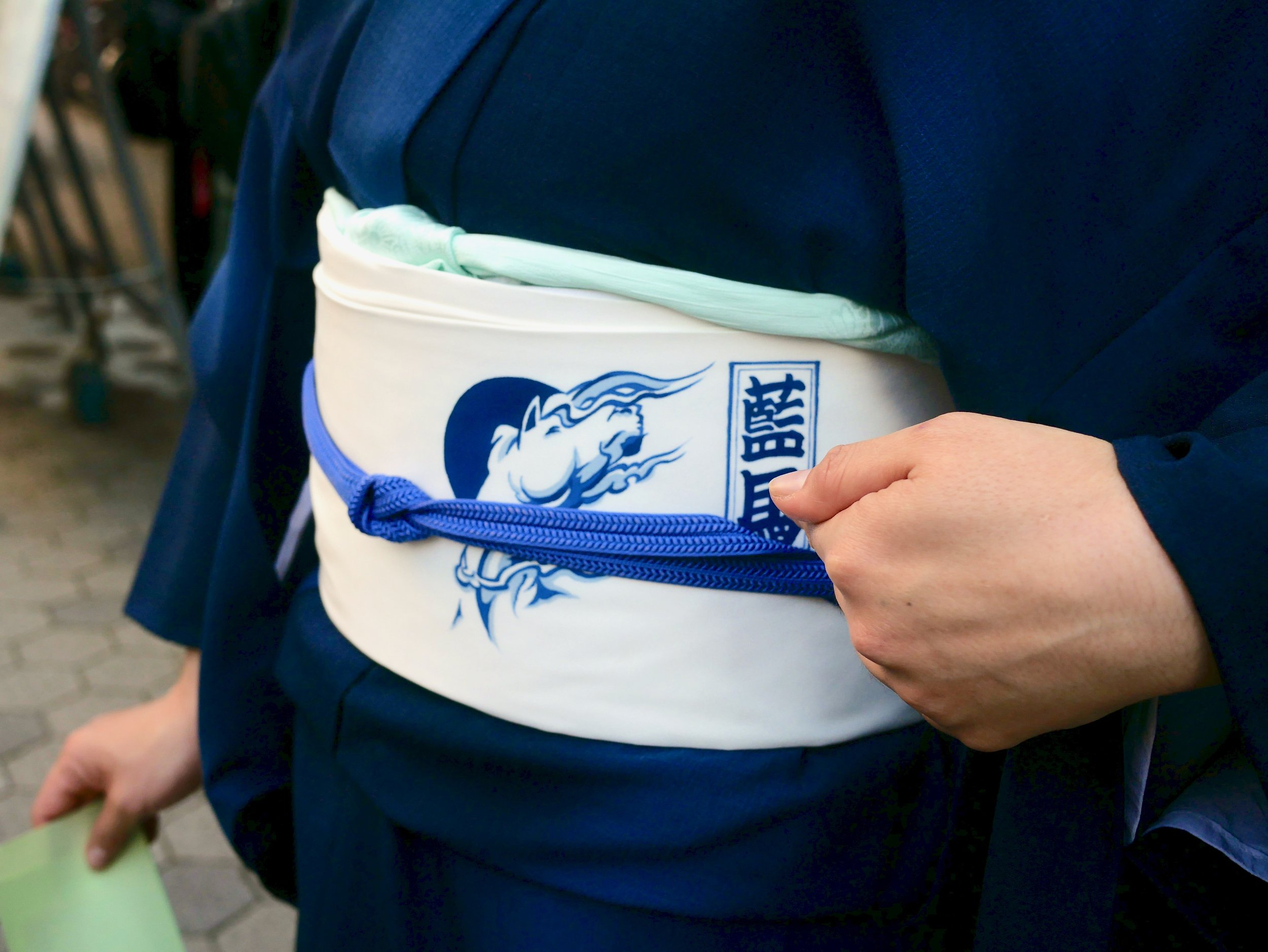 """Aiba shows off her custom-made  obi  with her signature logo of a """"dark horse"""" and her new name."""