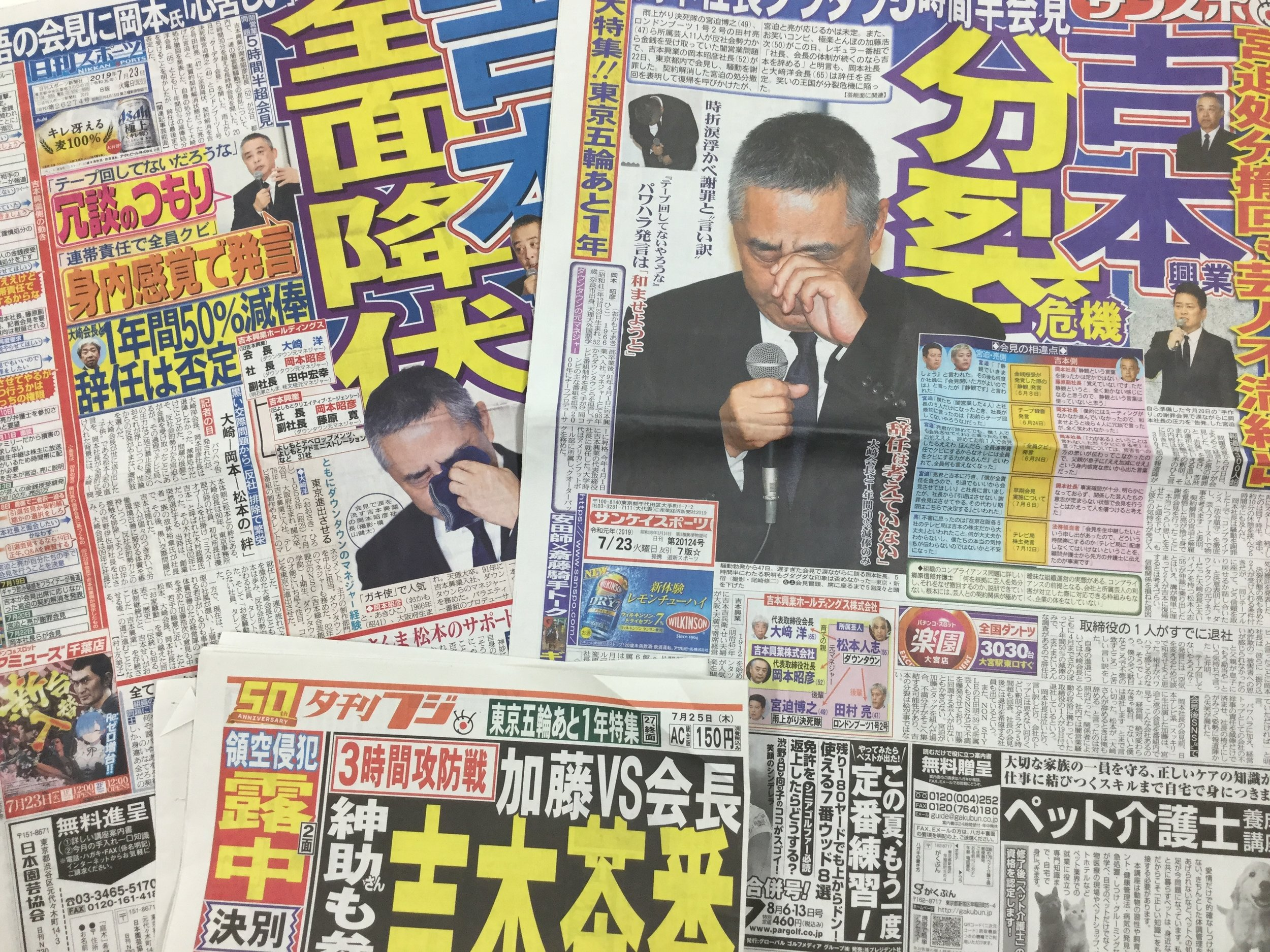 """Yoshimoto has dominated the news in the last week. After the press conference: newspapers with headlines of """"Full Surrender"""", """"Breakup Crisis"""", and """"Yoshimoto Farce""""."""