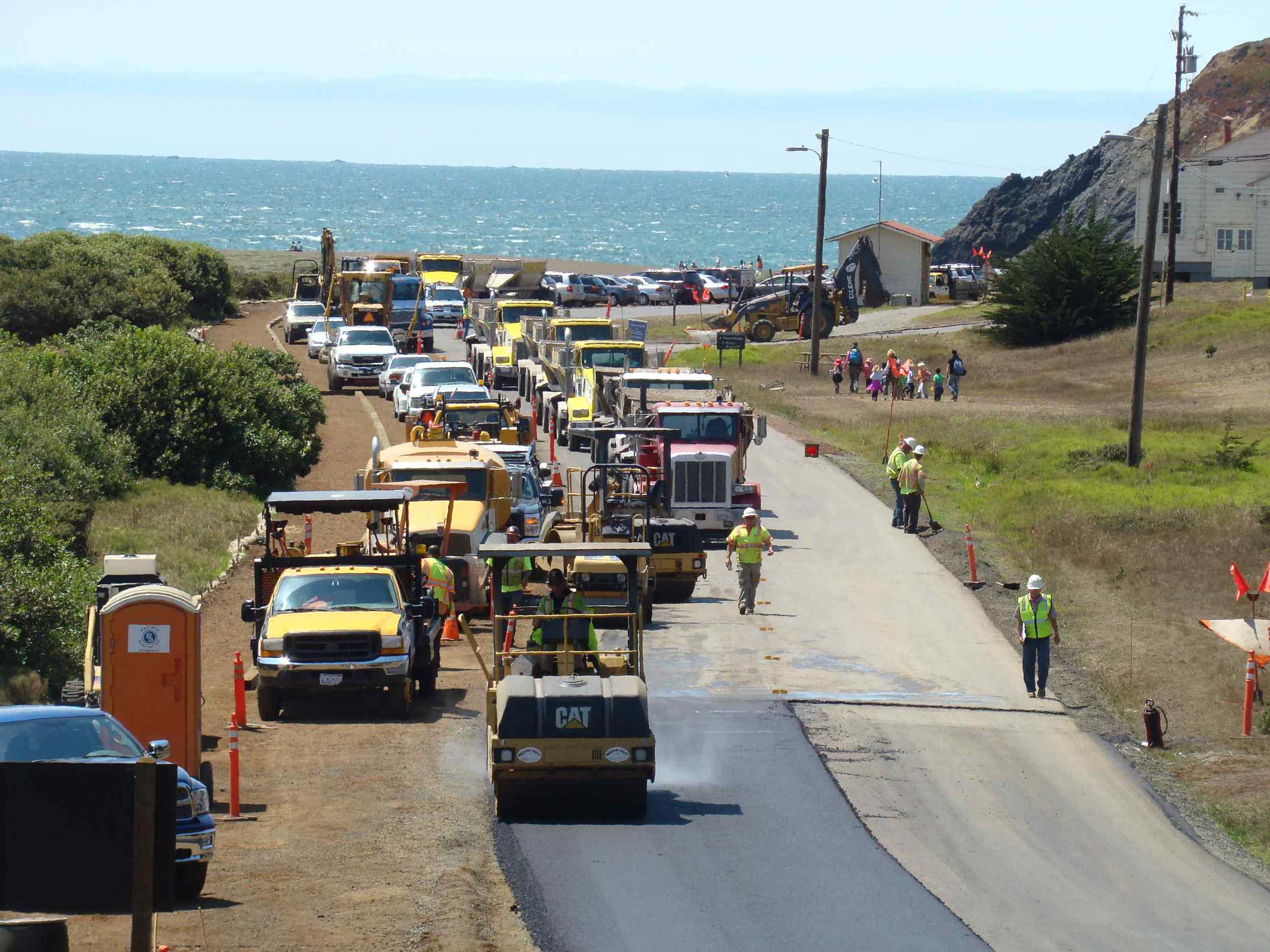 Line of bottom dumps ready to pave on Mitchell and Bunker Roads