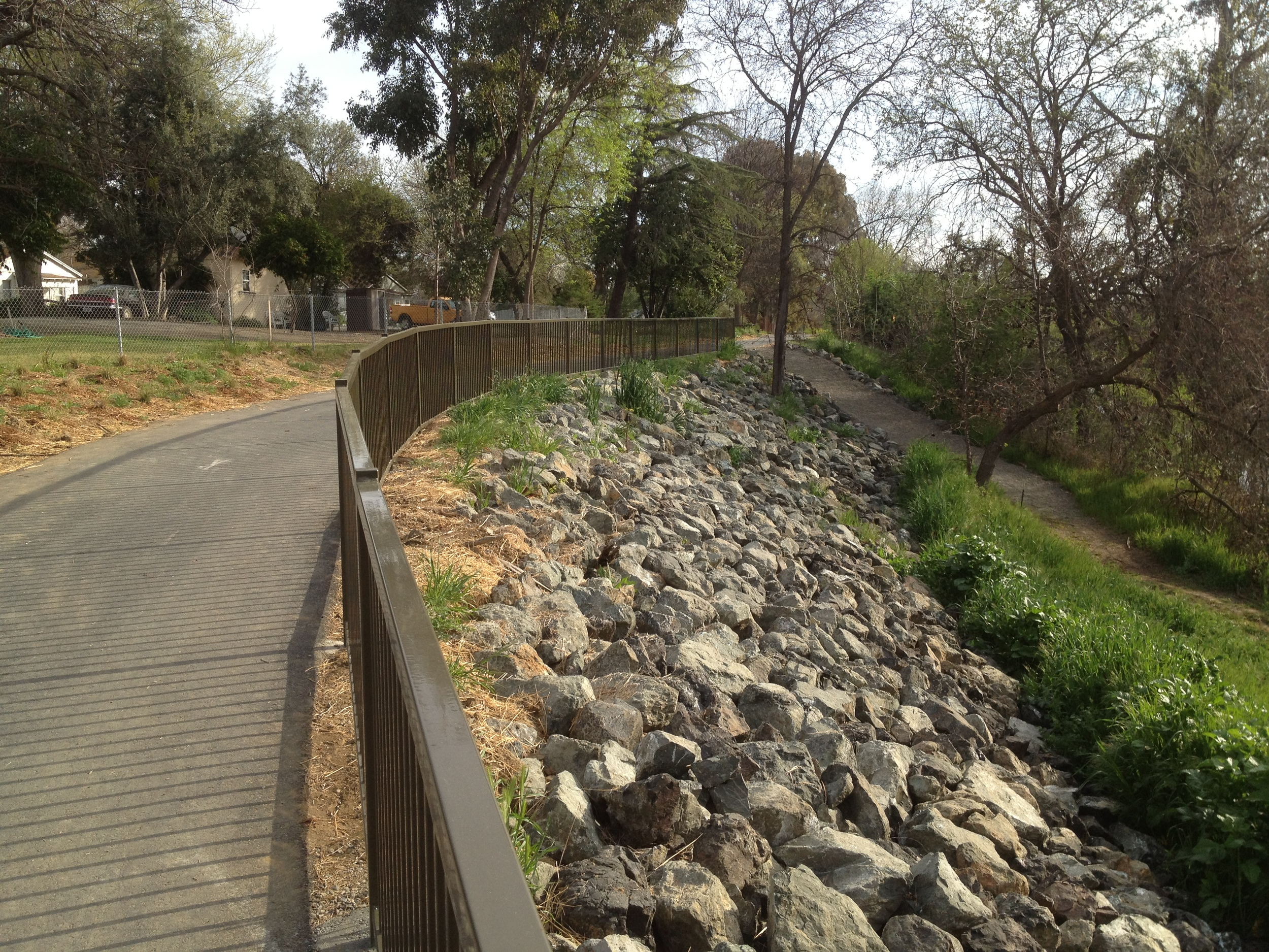 Pathway near community center with railing, Rip Rap slope and access path down to creek floodplain
